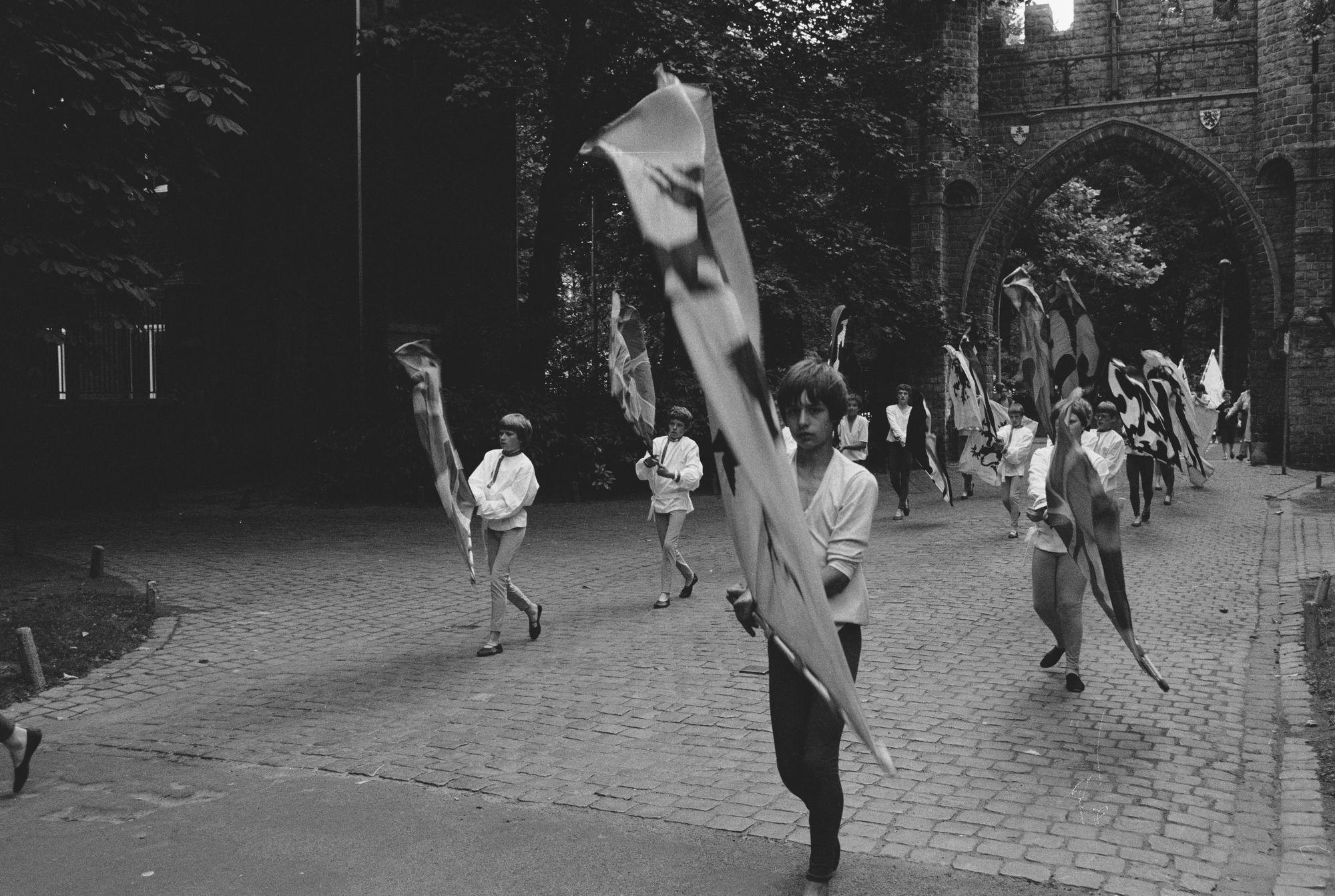 Vlaggenzwaaiers in optocht tijdens de 11 juliviering 1982