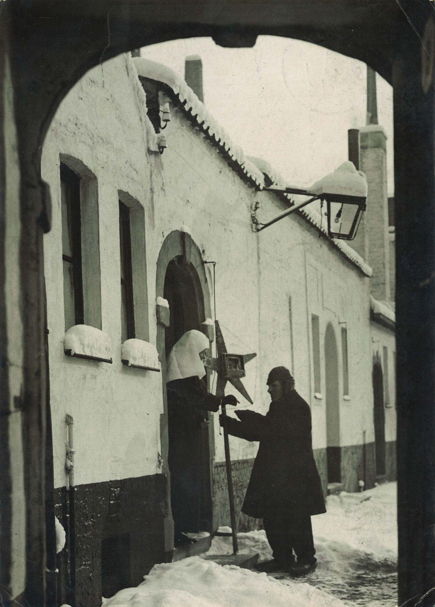 Bedelende man in het Begijnhof tijdens de Kerstperiode